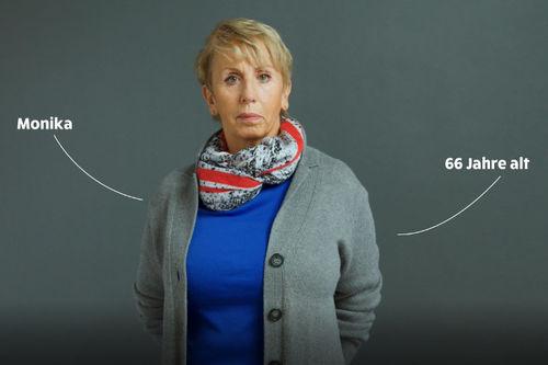 Monika 66 Jahre steht vor einem dunklen Hintergrund. Sie hat kurze blonde Haare und trägt ein blaues Shirt und eine graue Strickjacke.