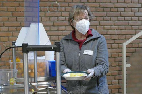 Pastorin Elisabeth Griemsmann mit Schutzmaske, Handschuhen und einem mit Essen gefülltem Teller in der Hand in der Ökumenischen Essenausgabe