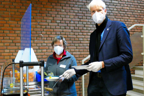 Zu sehen sind Pastorin Elisabeth Griemsmann, Evangelisch-reformierte Gemeinde Hannover und Stadtsuperintendent Rainer Müller-Brandes mit FFP2-Masken, die einen Teller und eine Suppenkelle in der Hand halten und in die Kamera schauen.