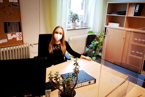 Projektleiterin Maria Lorentz sitzt mit Mund-Nasenschutz und hinter einer Plexiglasschreibe an ihrem Schreibtisch im Büro