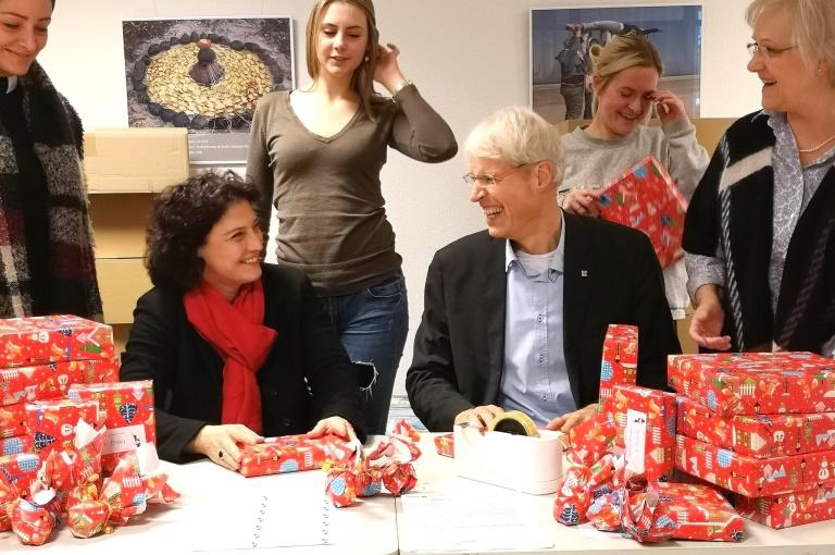 ministerin und diakoniepastor packen weihnachtsgeschenke. Black Bedroom Furniture Sets. Home Design Ideas